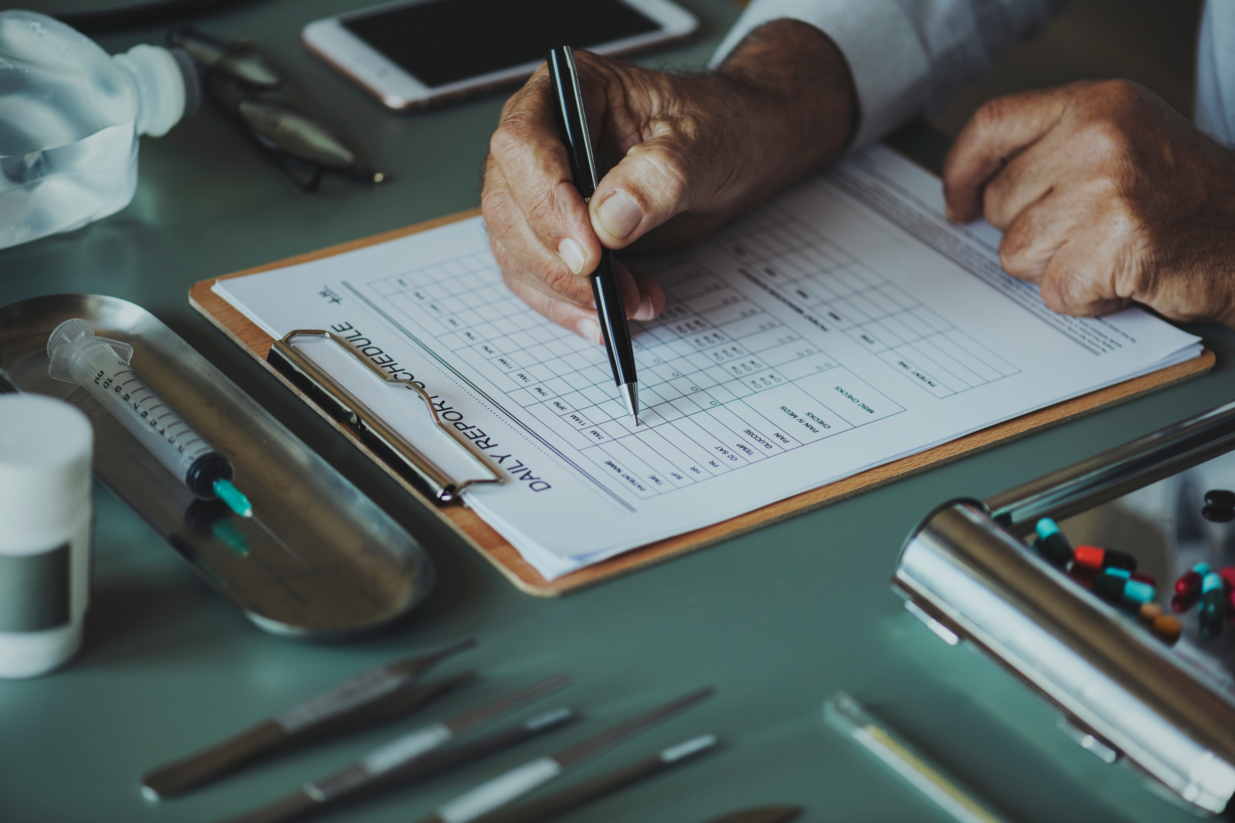 Man signing medical form with a pen